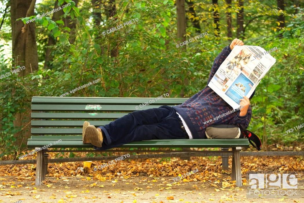 Stock Photo: Man reading a newspaper lying on a bench in Tiergarten.