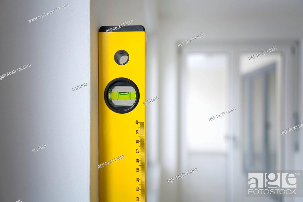 Stock Photo: Spirit level against wall in empty appartement.