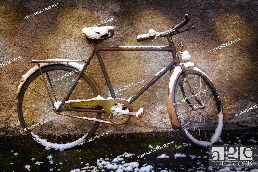 Stock Photo: Old forgotten bicycle under the snow on a wall, snow scene. Troinex, Geneva. Switzerland; Europe.