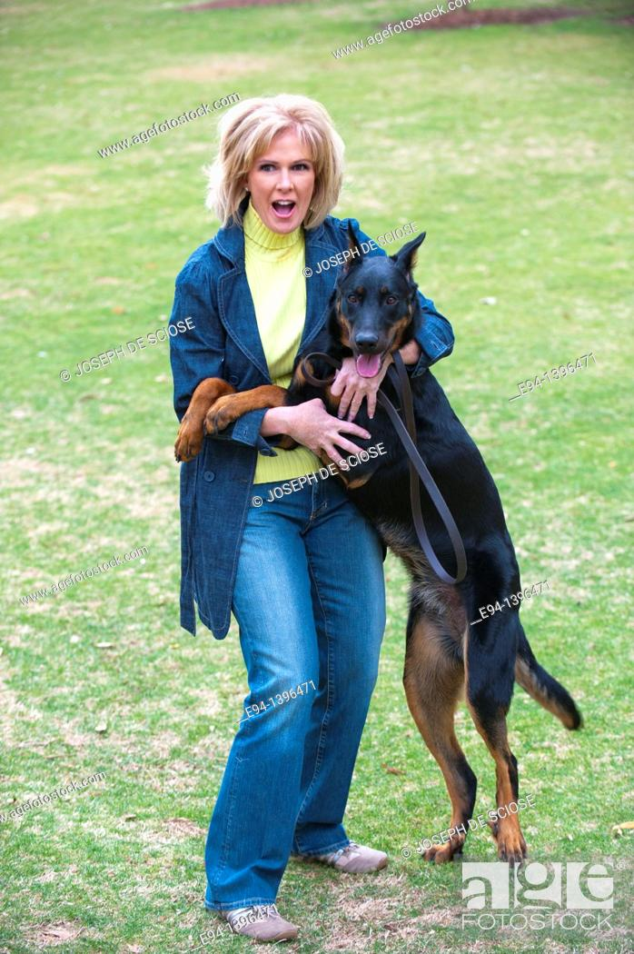 Stock Photo: Fifty year old blond woman playing with a Doberman Pinscher in a park.