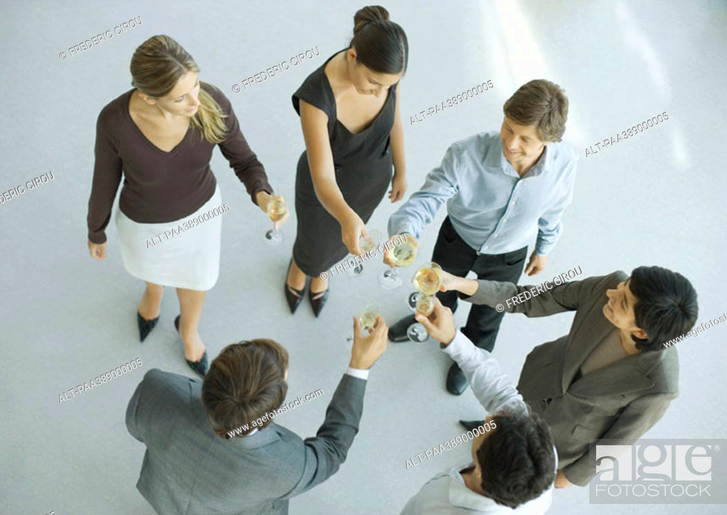 Stock Photo: Young executives raising glasses for toast, high angle view.