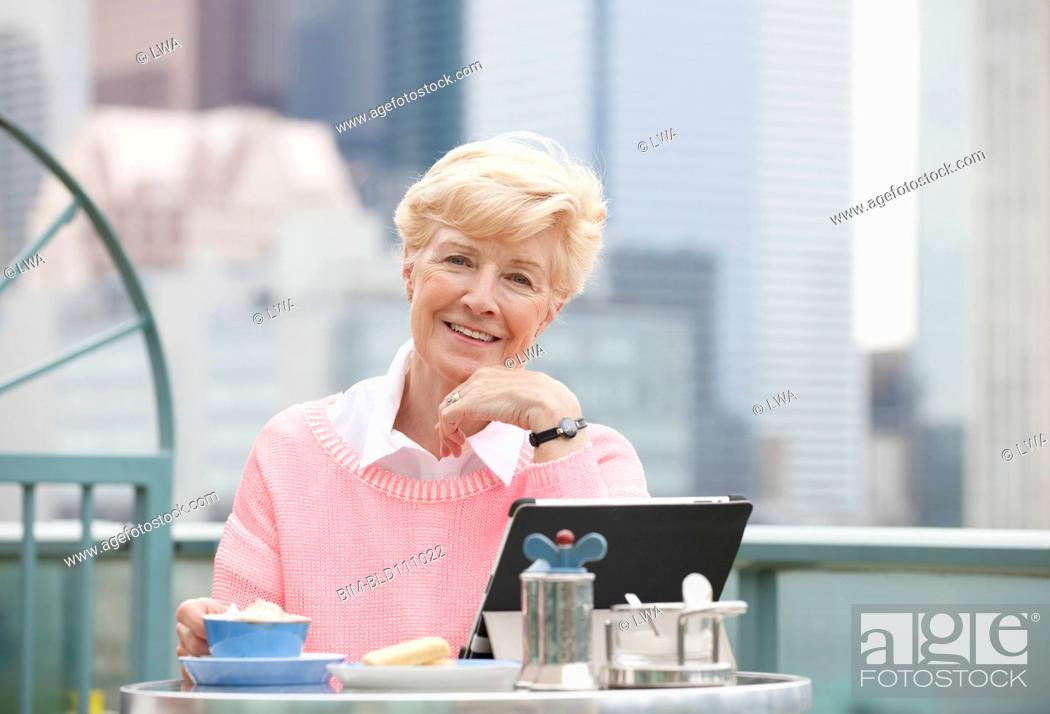 Stock Photo: Caucasian woman using laptop in cafe.