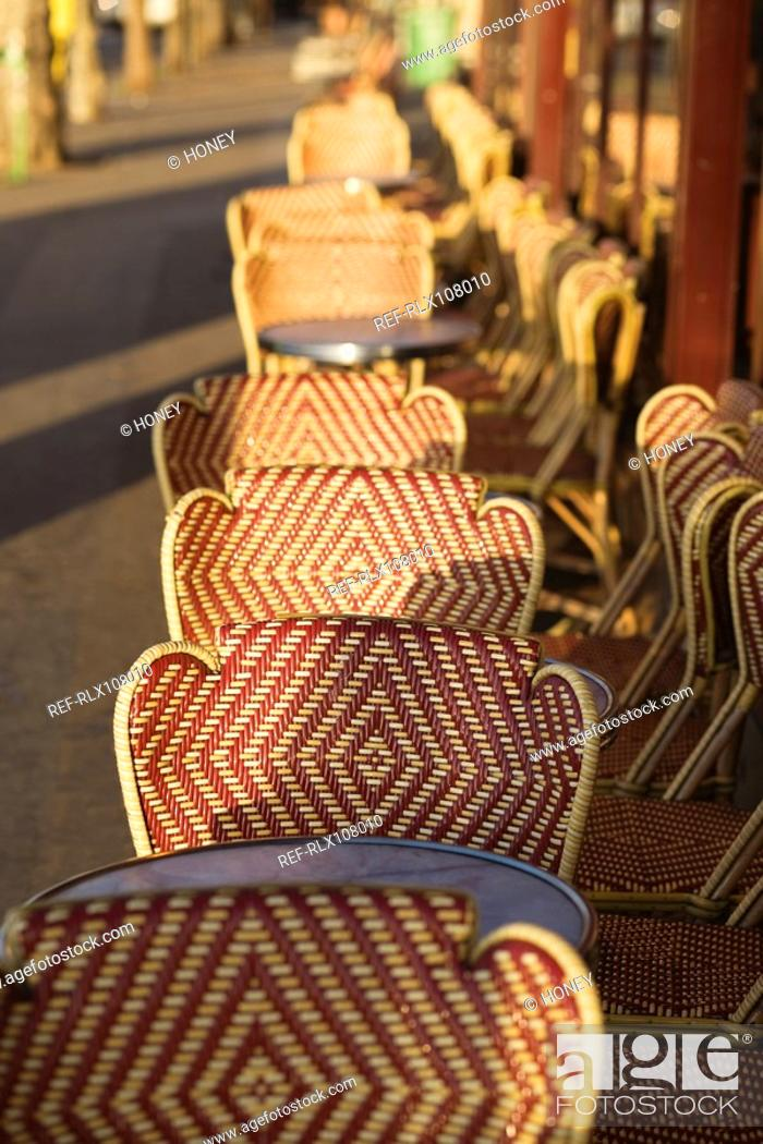 Stock Photo: Row of wicker chairs and tables outside cafe, Paris, France.