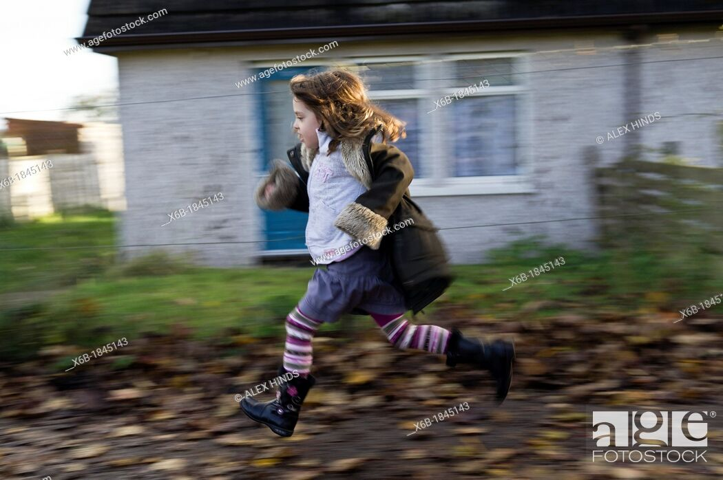 Stock Photo: Six year old girl running along residential pavement covered in Autumn leaves.