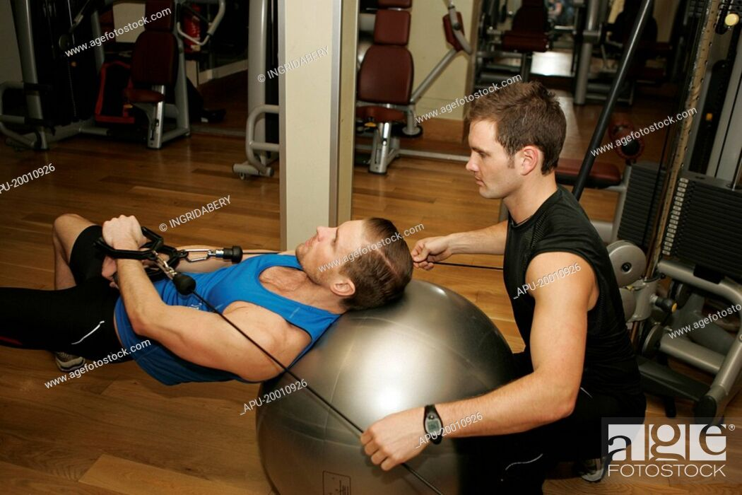 Imagen: Man working out on exercise ball with spotter.