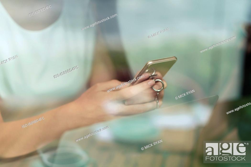 Stock Photo: Businesswoman using smartphone and laptop, mid section, close-up.
