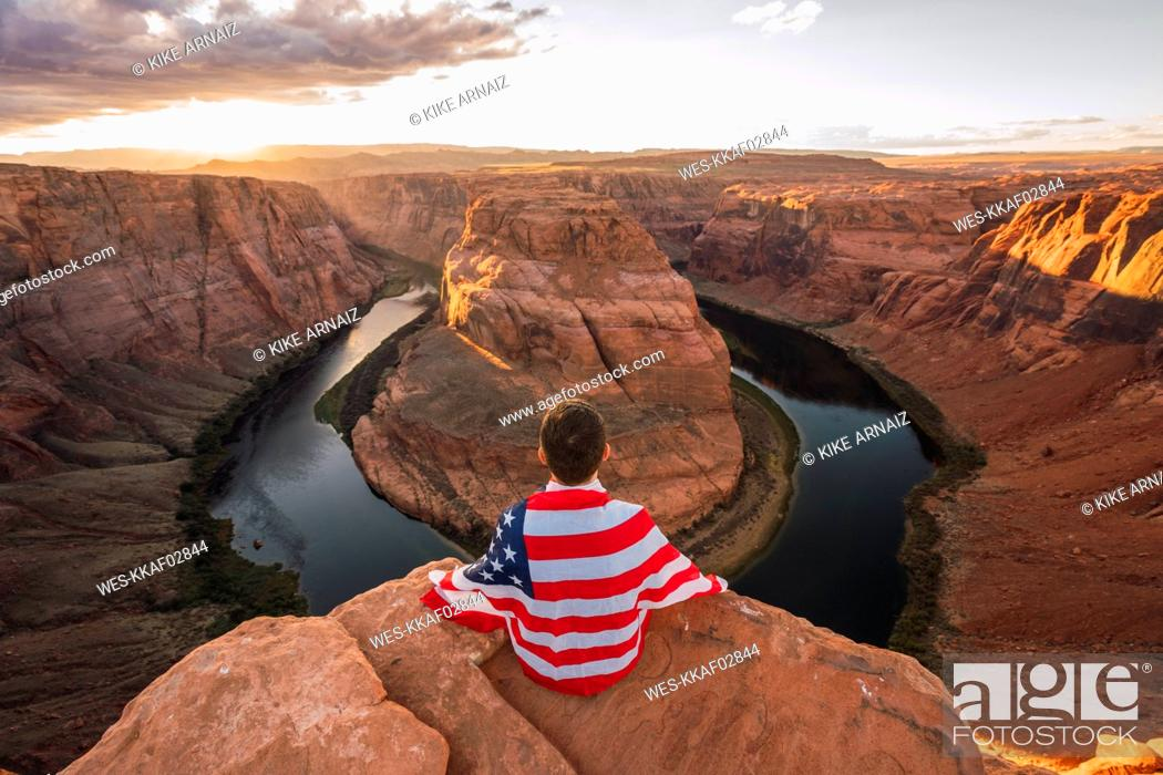 Photo de stock: USA, Arizona, Colorado River, Horseshoe Bend, young man sitting on viewpoint with American flag.