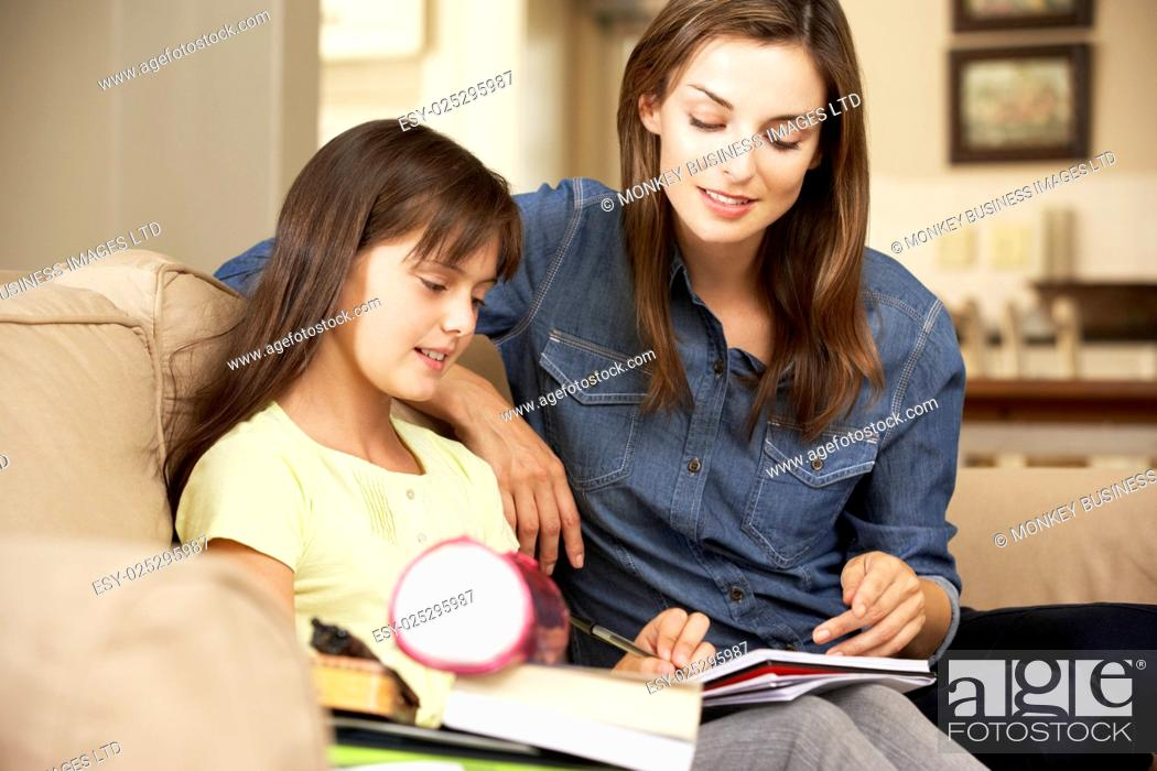 Stock Photo: Mother Helping Daughter With Homework Sitting On Sofa At Home.