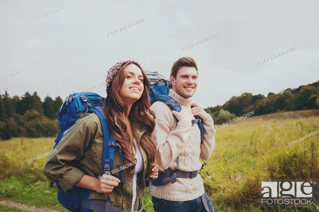 Photo de stock: adventure, travel, tourism, hike and people concept - smiling couple walking with backpacks outdoors.