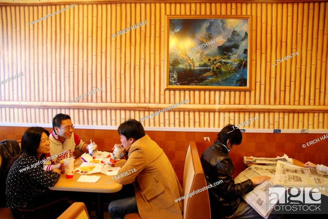 Stock Photo: Young Chinese People eating Burgers in a Mc Donalt Restaurant in Chinatown.