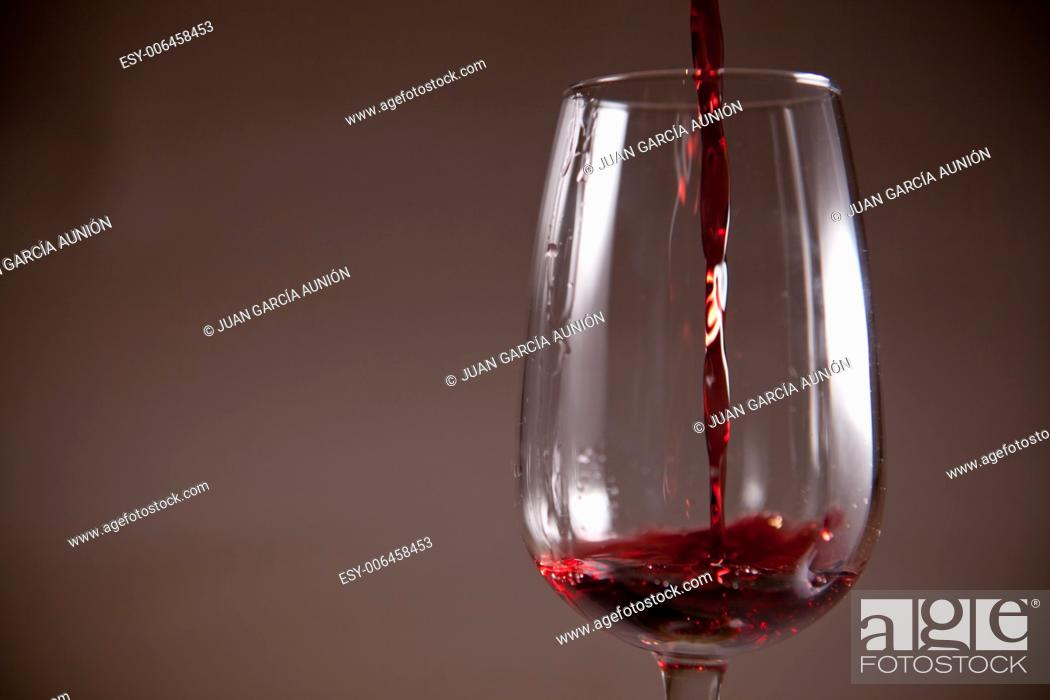 Stock Photo: Glass with red wine poured on a cup. Isolated over dark background.