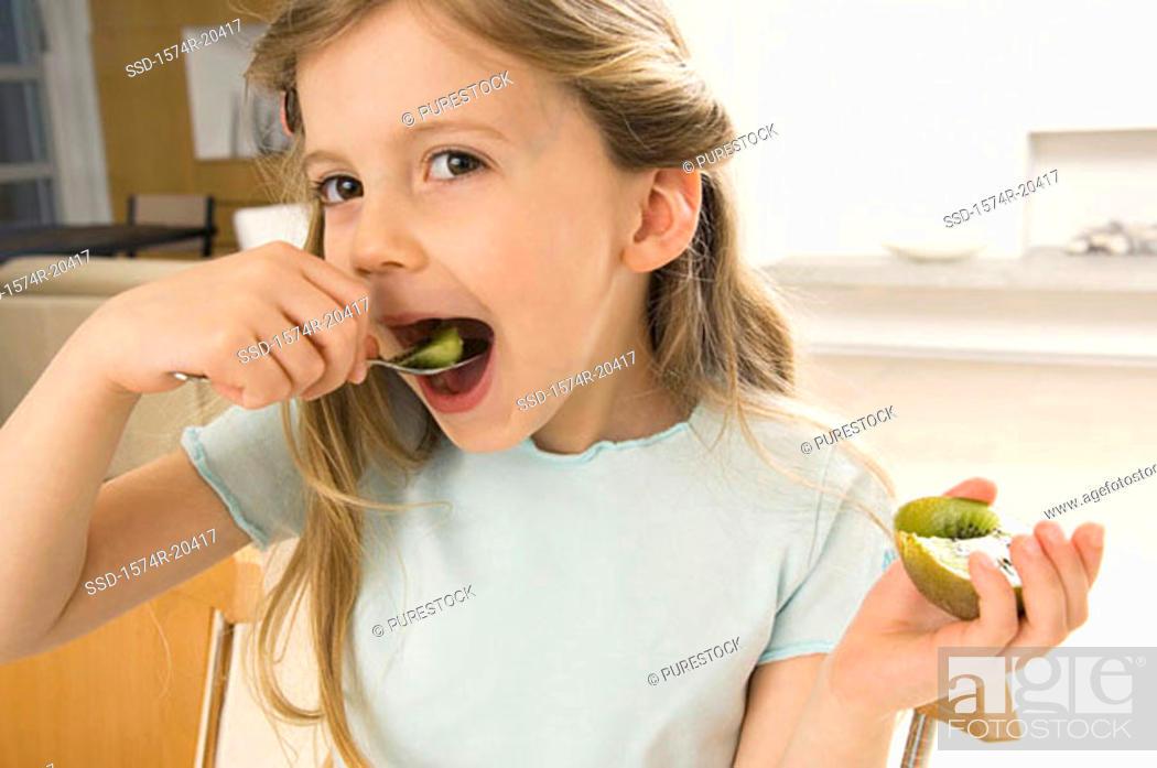 Stock Photo: Portrait of a girl eating a kiwi.