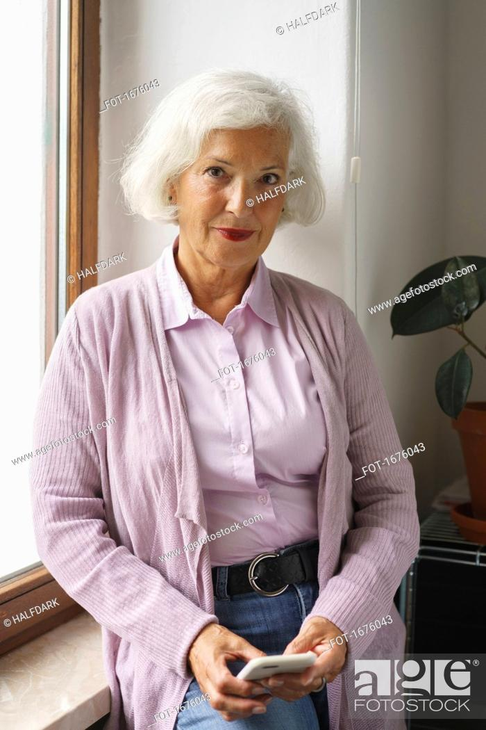 Stock Photo: Portrait of senior woman with mobile phone leaning on window sill at office.