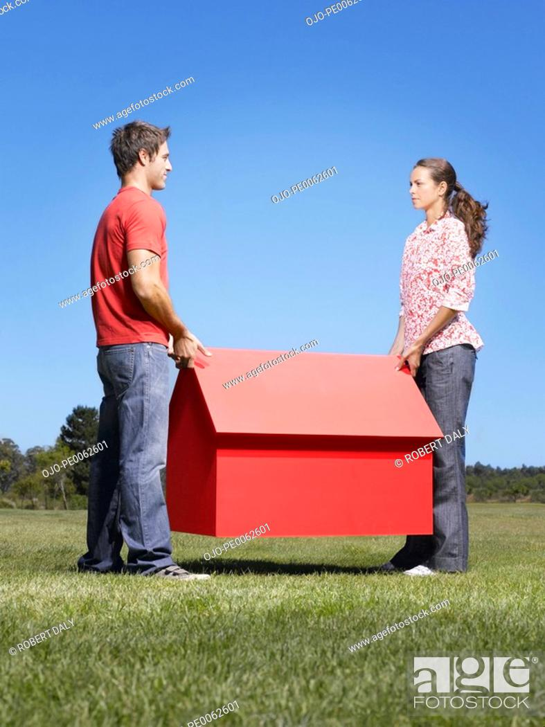 Stock Photo: Couple holding small model house.