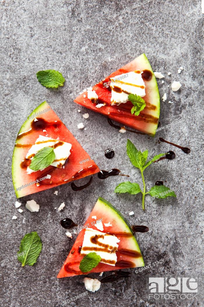 Stock Photo: Three slices of fresh watermelon topped with feta cheese, balsamic syrup and fresh mint leaves.