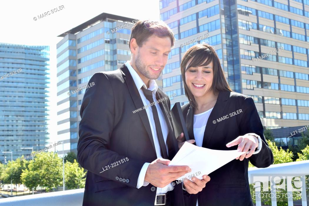 Imagen: Businessman and businesswoman look over paperwork while standing outside.