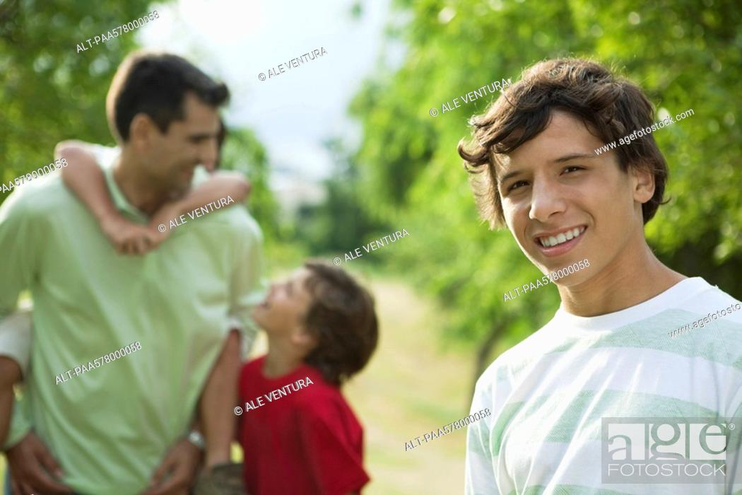 Stock Photo: Teenage boy outdoors with father and younger brothers, portrait.