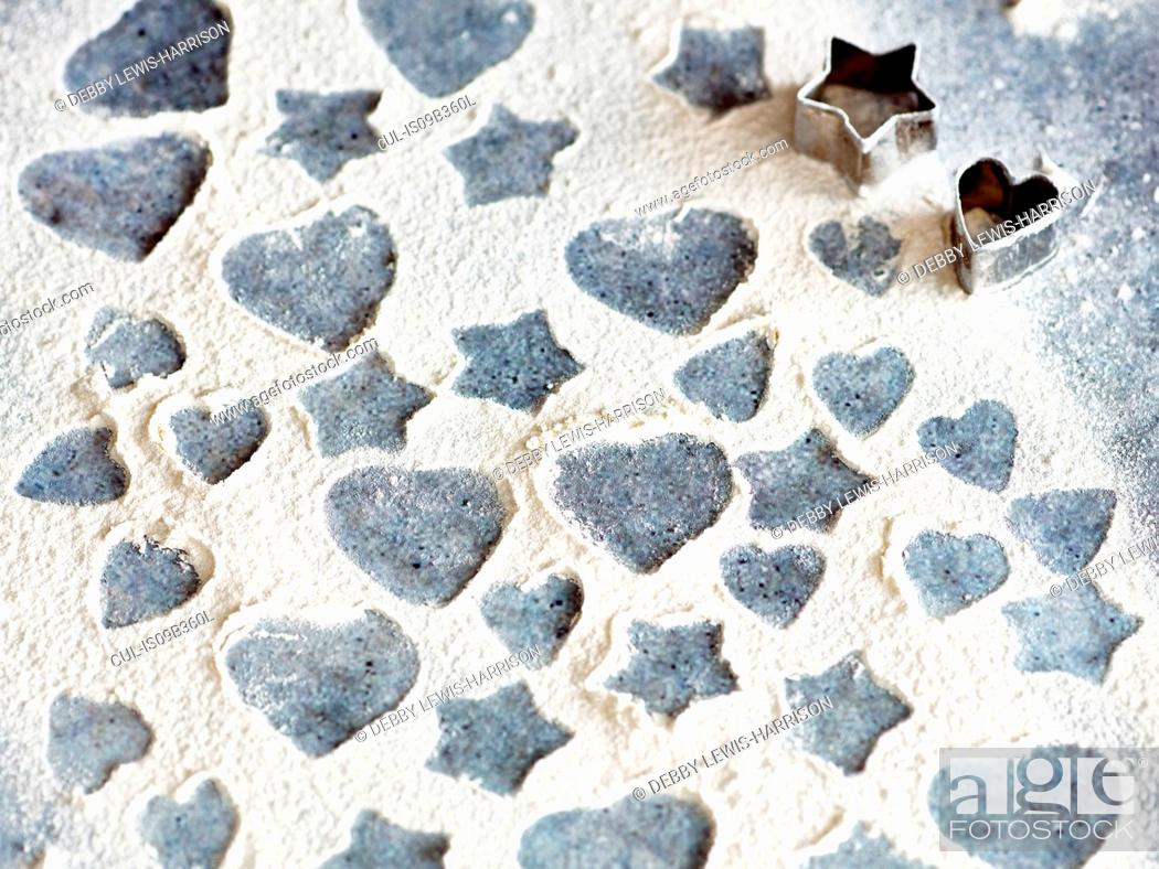 Stock Photo: Heart and star shapes patterns in flour with cookie cutters.