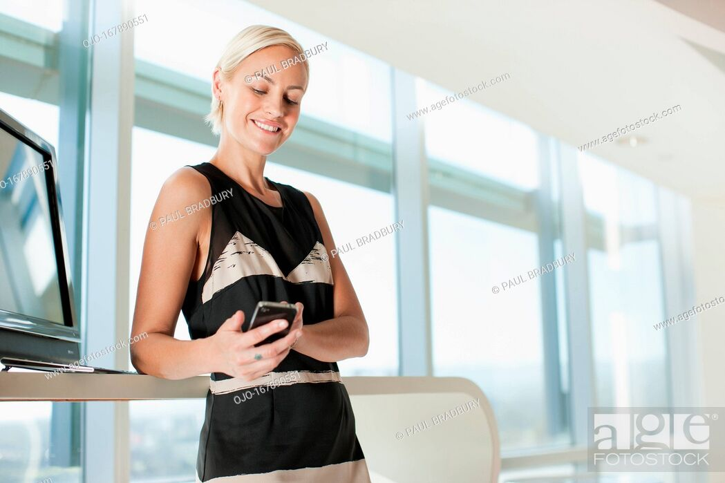 Stock Photo: Businesswoman using cell phone in office.