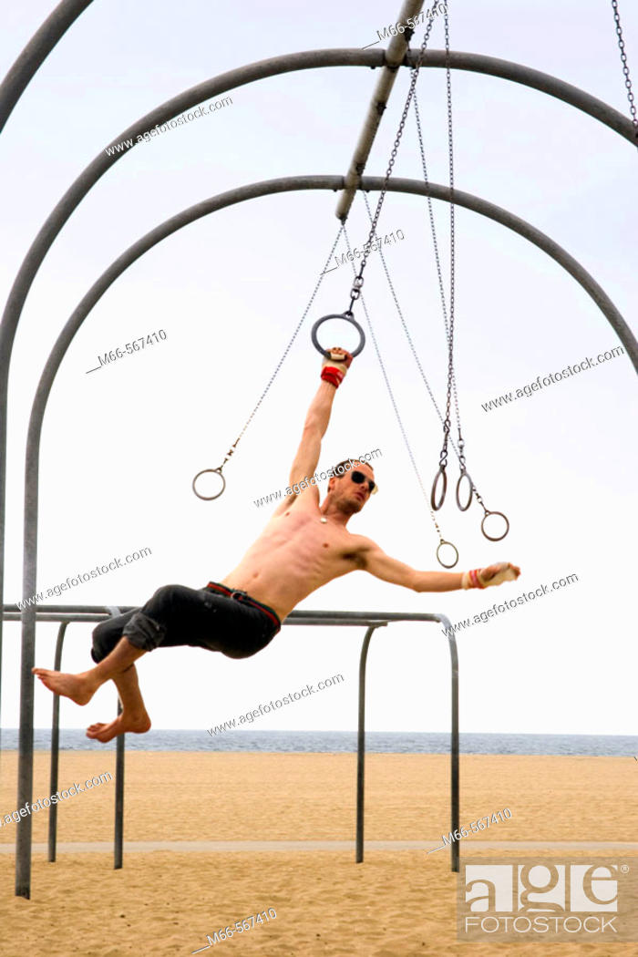 Stock Photo: Caucasian man on the rings set, swinging from one ring to the next. Santa Monica Beach, Los Angeles, California.