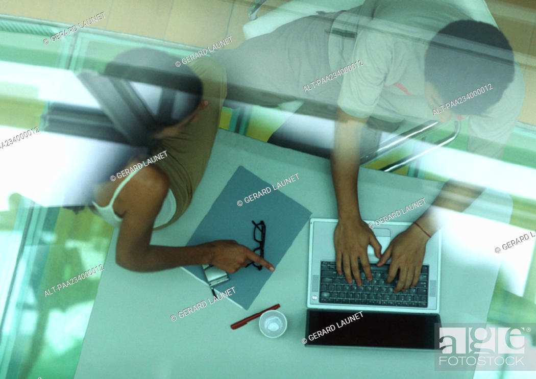 Stock Photo: Man working on laptop, woman sitting on table pointing at laptop, through glass, high angle view.