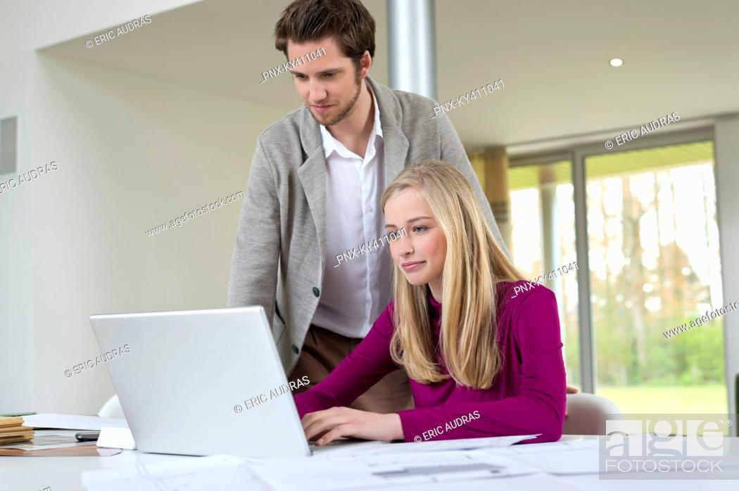 Stock Photo: Man looking at a woman working on a laptop.
