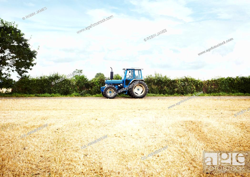 Stock Photo: Tractor driving in tilled crop field.