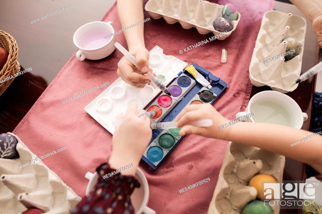 Stock Photo: Children painting Easter eggs on table at home.