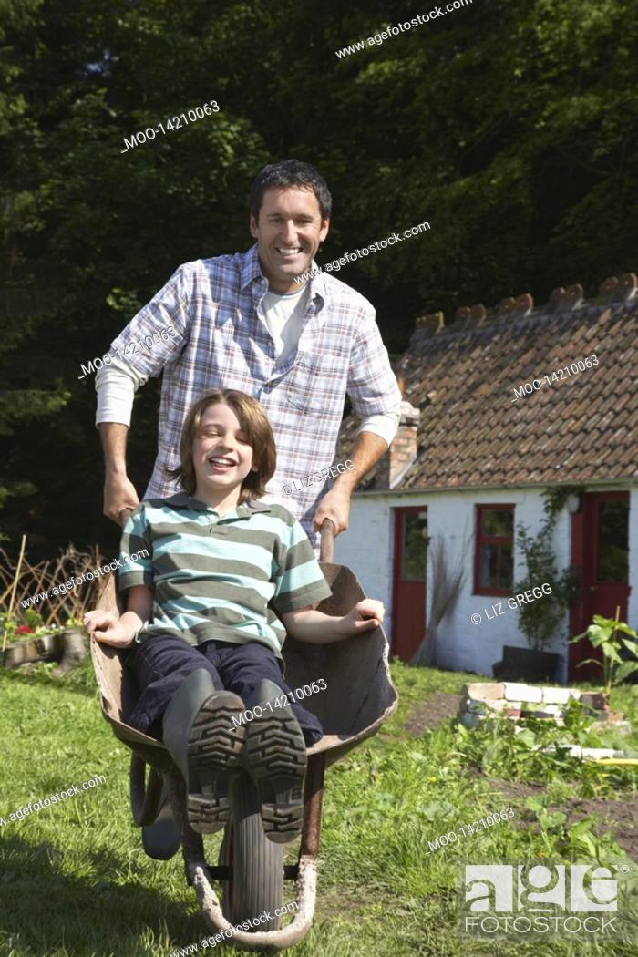 Stock Photo: Father pushing son 7-9 in wheelbarrow outside cottage portrait.