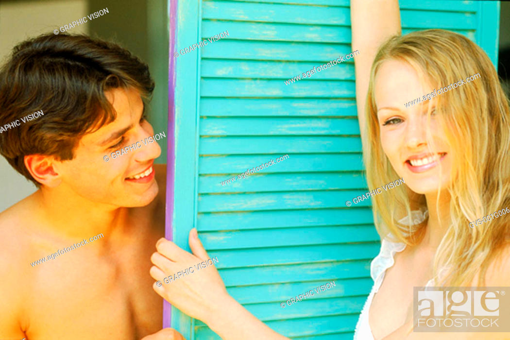 Stock Photo: Portrait of young woman standing against a shutter with a young man.