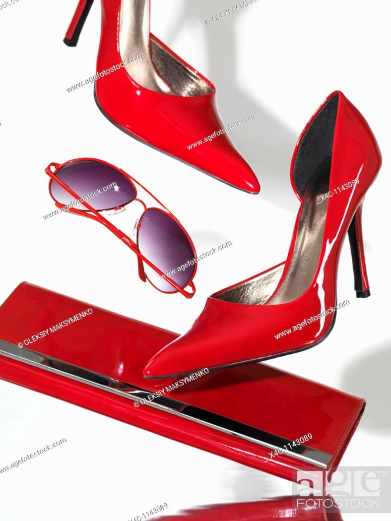 Stock Photo: Stylish red high heel stiletto shoes sunglasses and a clutch hand bag falling on metal surface with white background behind.