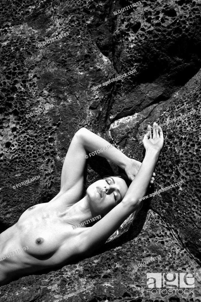 Stock Photo: Close up of young adult nude woman laying on rocks.