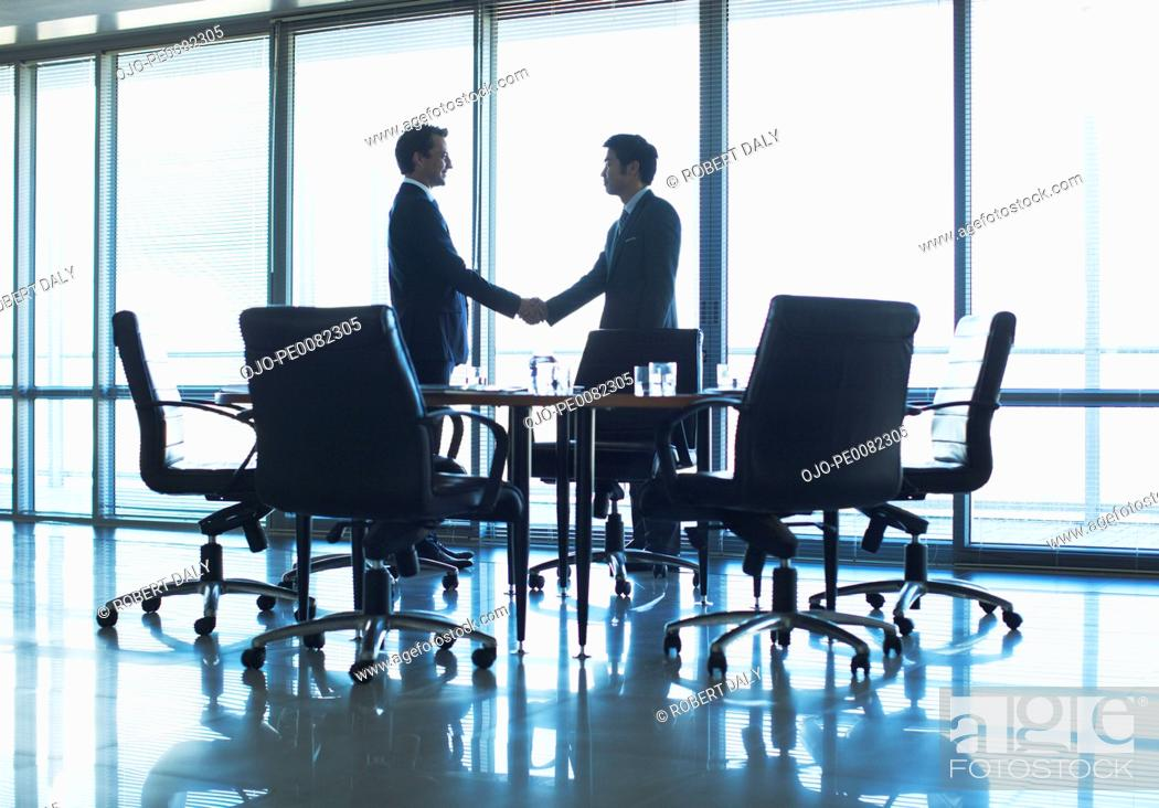Stock Photo: Silhouette of businessmen shaking hands in conference room.