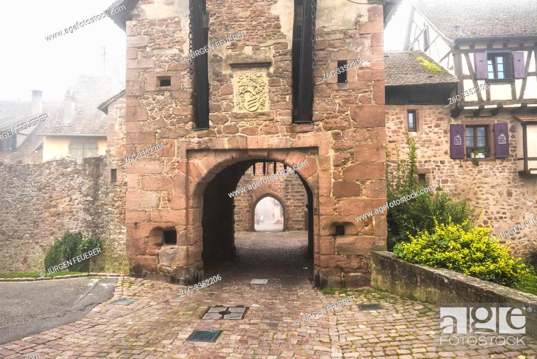 Stock Photo: medieval rampart and town gate of village Riquewihr with fog, Alsace, France, touristy village of the Wine Route.