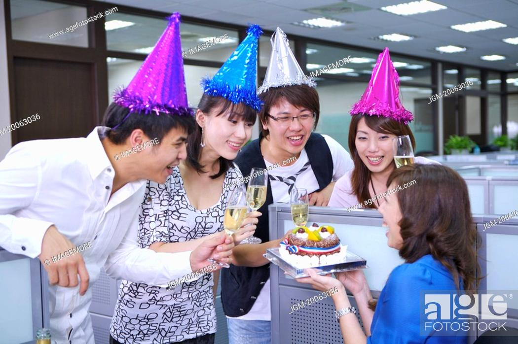 Stock Photo: Colleagues wearing headwear and toasting for celebrating.