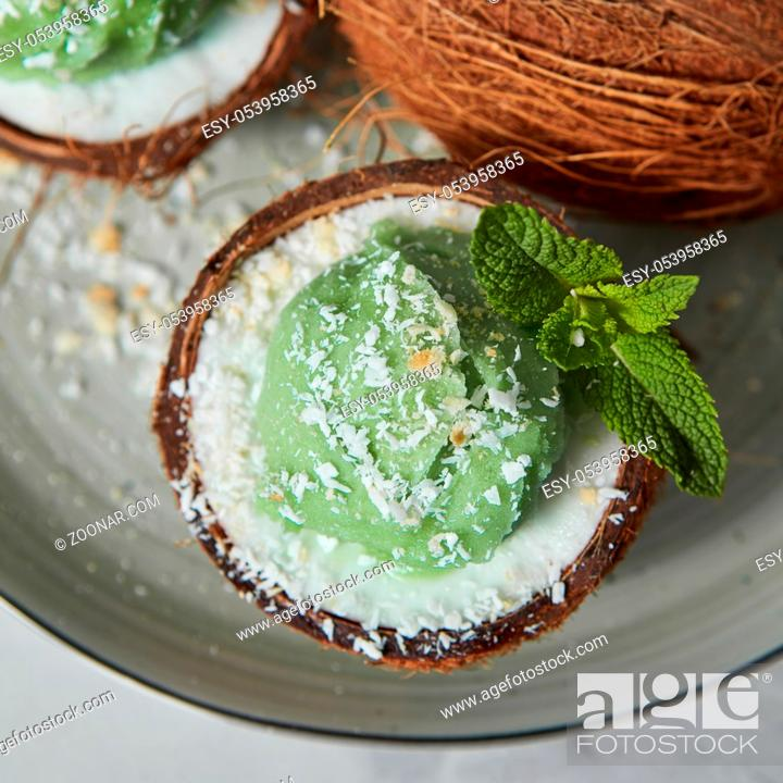 Stock Photo: Homemade green ice cream in a coconut shell, mint leaf on a gray ceramic plate on a light gray. Top view. Vegetarian concept of diet eating.