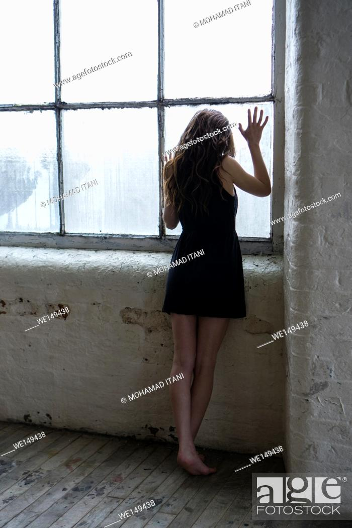 Stock Photo: Barefooted woman in black dress standing by the window.
