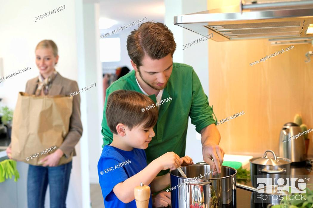 Stock Photo: Boy and his father cooking in the kitchen while mother carrying a grocery bag.