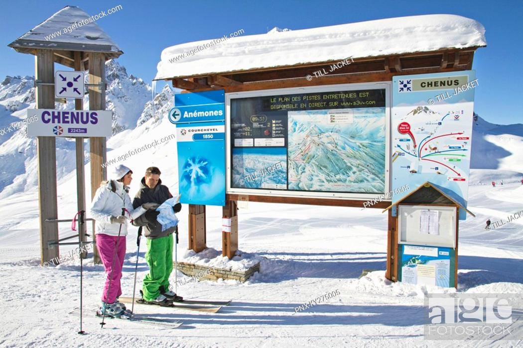 Stock Photo: Couple of skiers looking at map, Courchevel, France.