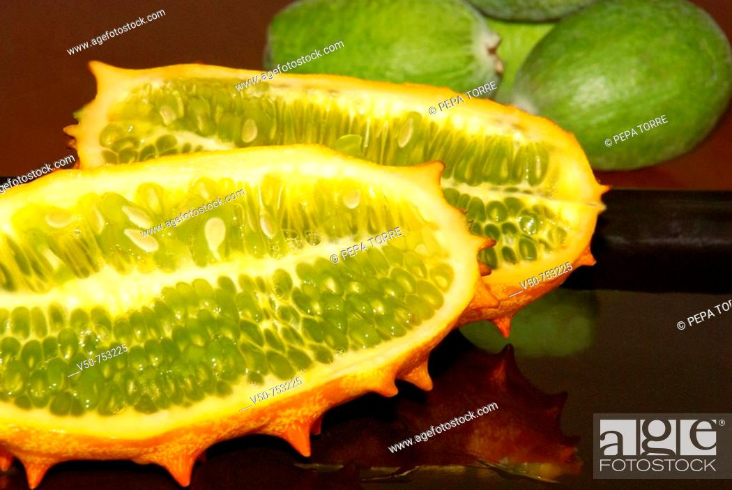 Stock Photo: Kiwiano Fruit close up cut in half and feijoa fruits in the background.