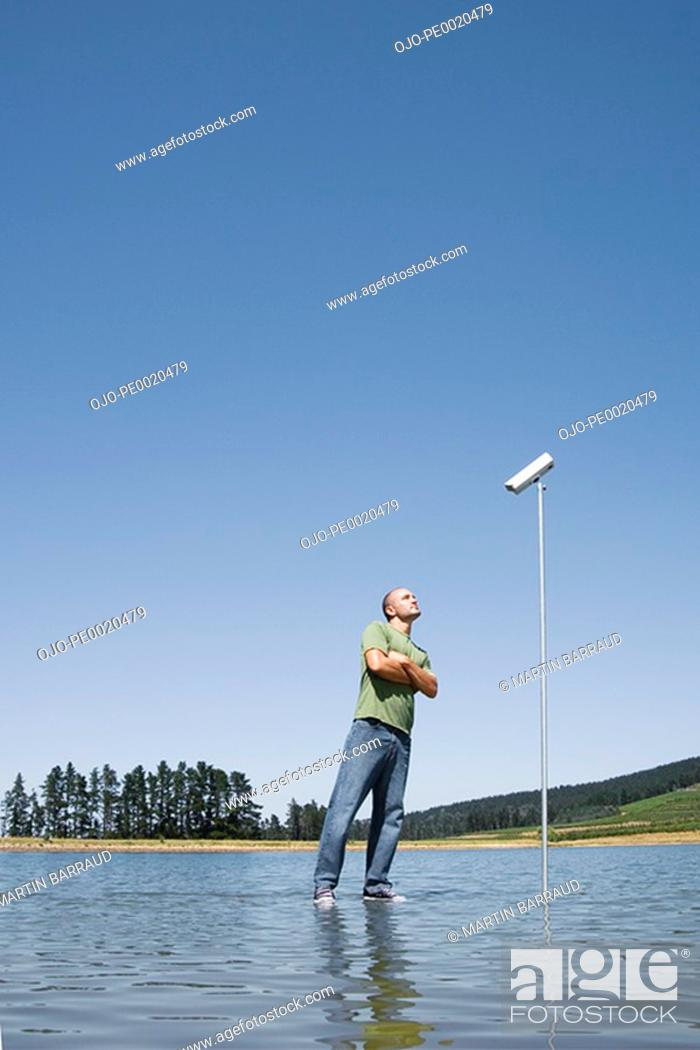 Stock Photo: Man standing on water with surveillance camera.