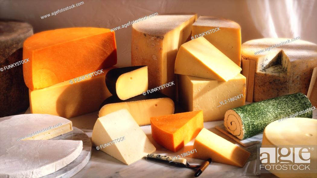 Stock Photo: British cheese shop photo A selection of Cheeses, From left, Red Leicester cheese on top of Leicester cheese, in the black wax, Dutch cheese.