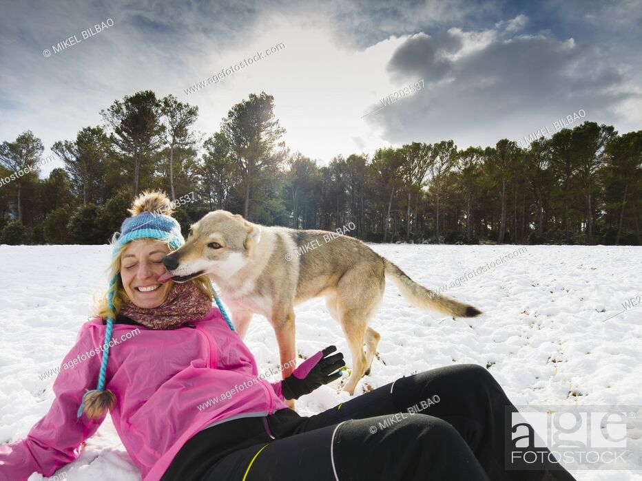 Stock Photo: Caucasian young woman with hat and raincoat and wolf dog enjoying snow outdoor in winter time. Navarre, Spain, Europe.
