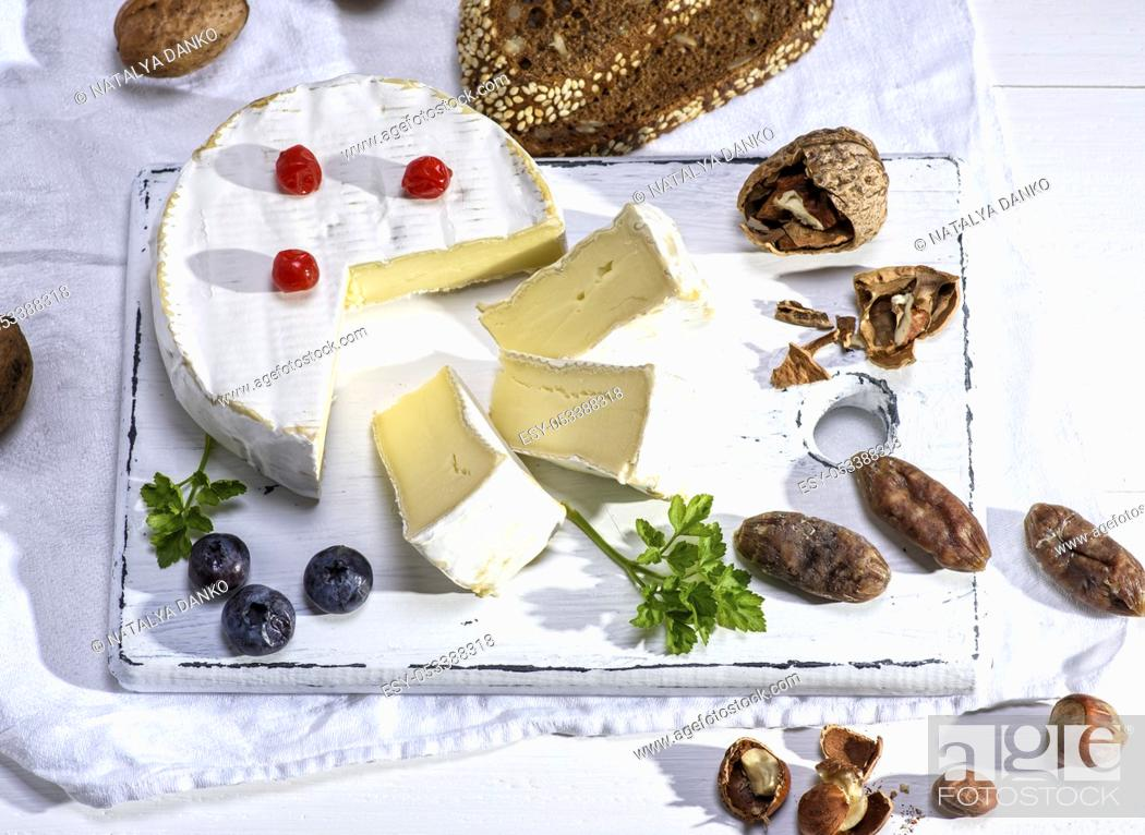 Stock Photo: round Camembert cheese on a white wooden board, next to sausage and nuts, white wooden table, top view.