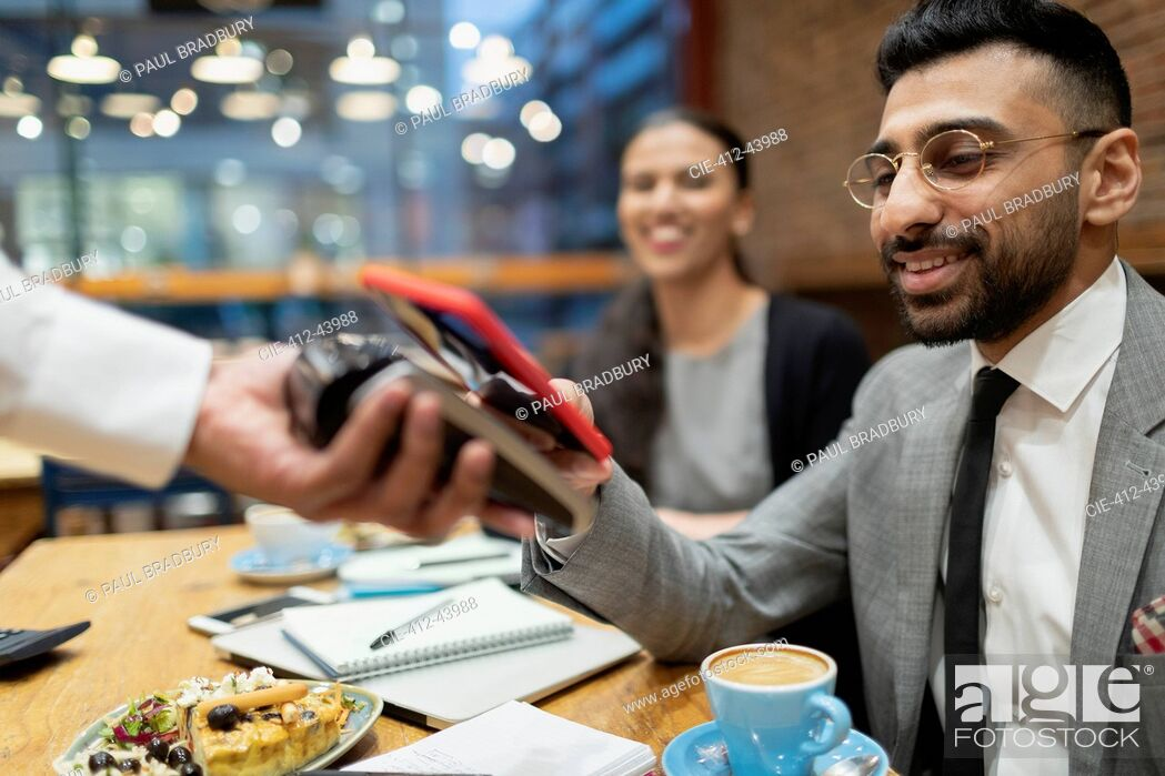 Stock Photo: Businessman paying with smart phone contactless payment in cafe.