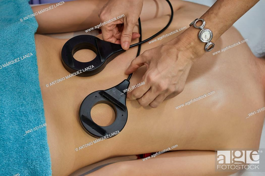 Stock Photo: Magnet therapy - Physical therapist placing magnets for treatment of patient's back with blue towel.
