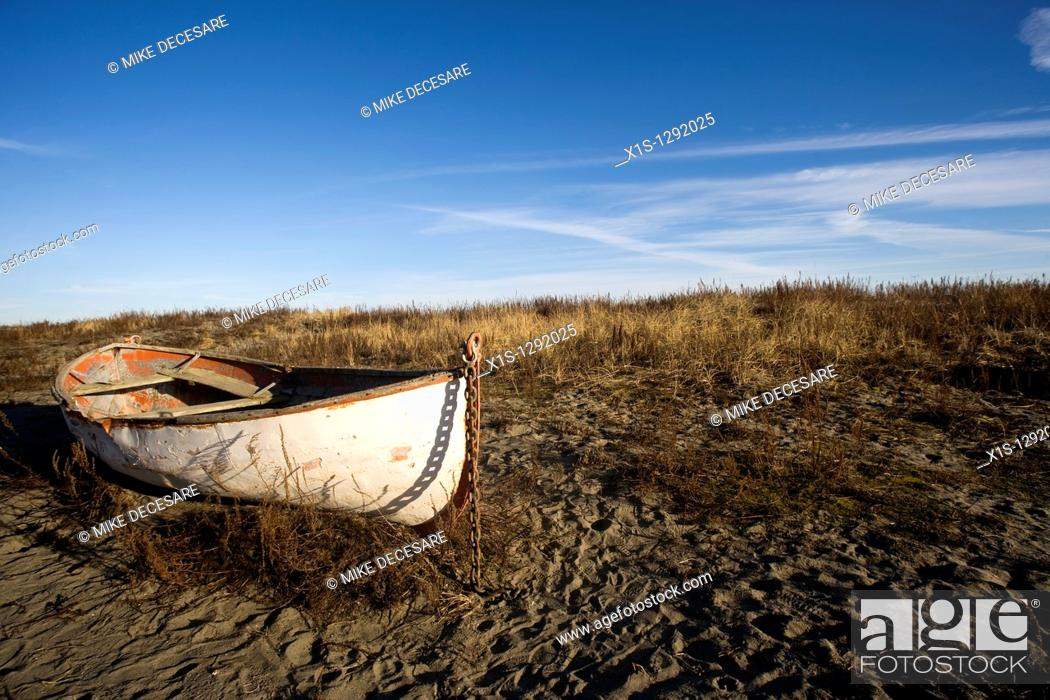 Photo de stock: An old wooden lifeboat is beached in the sand of a nondescript location under blue skies.