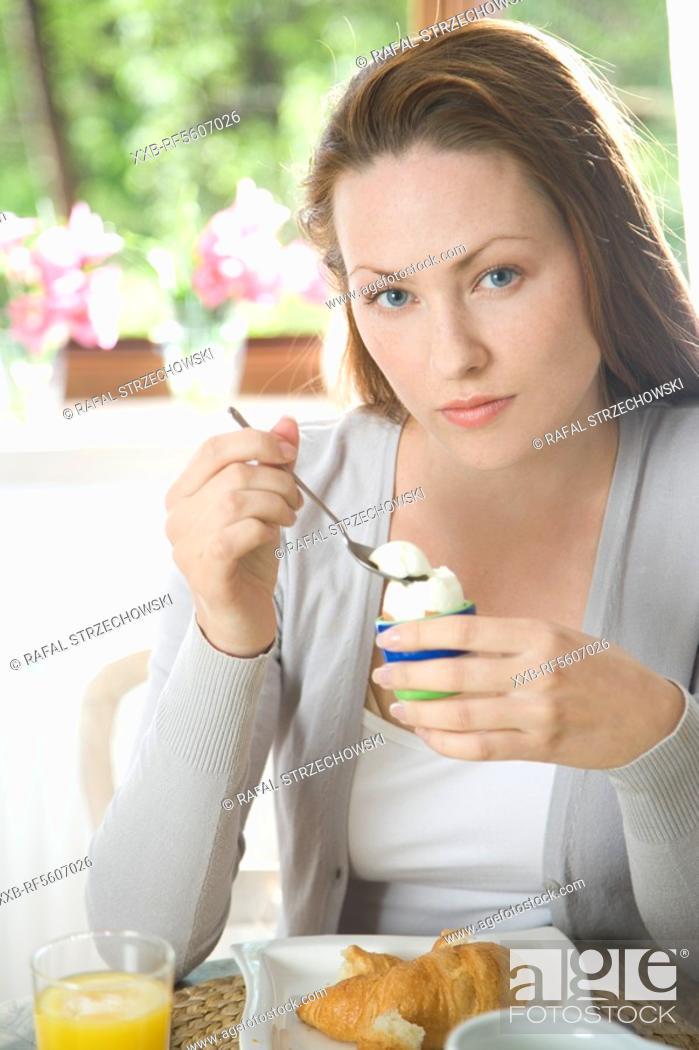 Stock Photo: woman eating egg for breakfast.