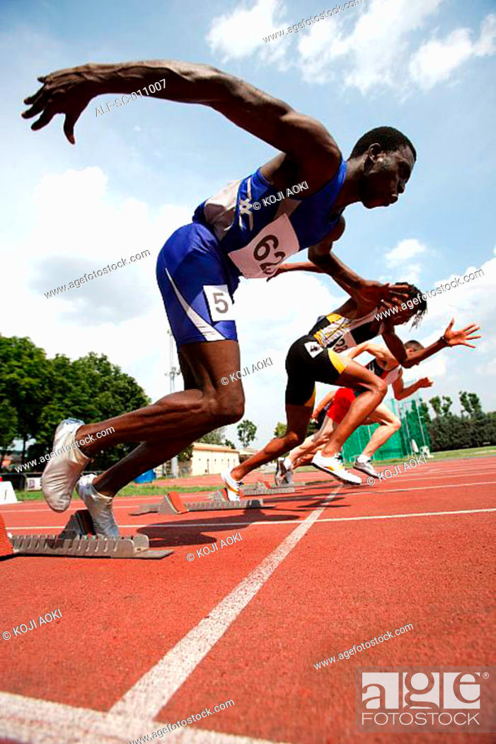 Stock Photo: Male Runners Leaping Off Starting Blocks.