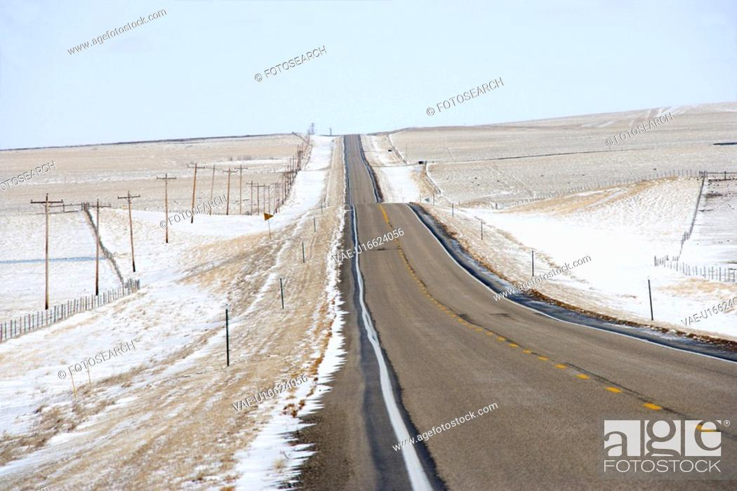 Stock Photo: Road over rolling hill landscape with snow and power lines.